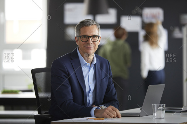 Portrait of businessman at desk in office with colleagues in background