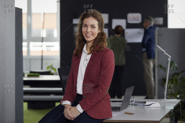 Portrait of smiling businesswoman sitting on desk in office with colleagues in background