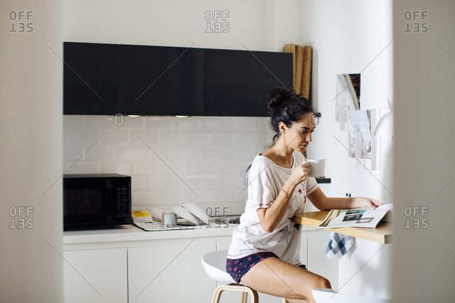 Young woman reading a magazine and drinking coffee in kitchen