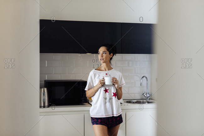 Young woman in the morning in kitchen