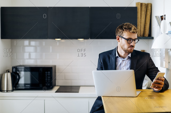 Young businessman using laptop and cell phone in kitchen