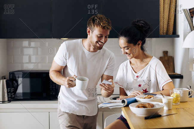 Happy young couple in the kitchen looking at cell phone