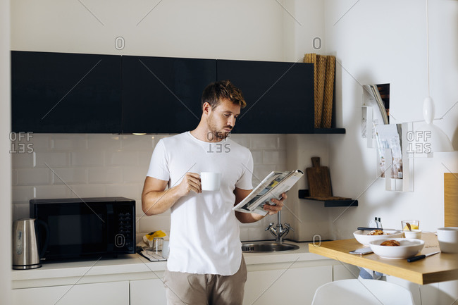 Young man reading a magazine and drinking coffee in kitchen