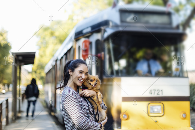 Happy young woman with dog at tram station in the city