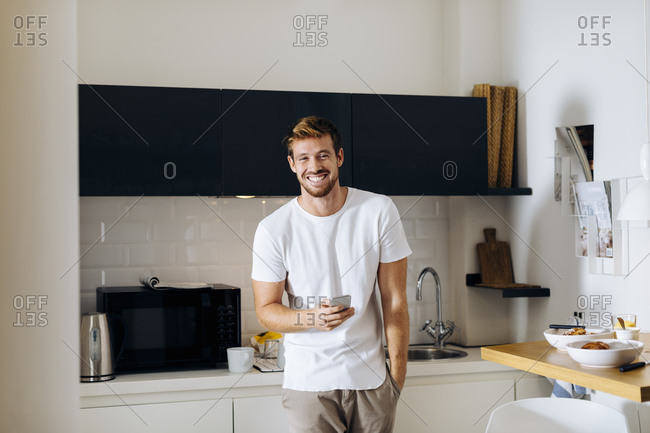 Portrait of happy young man holding cell phone in kitchen