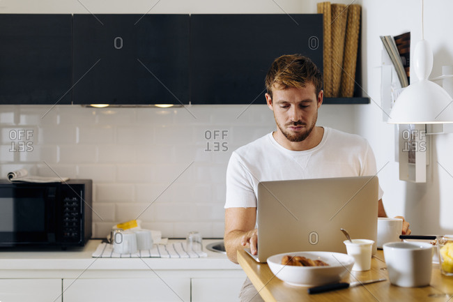 Young man using laptop in kitchen