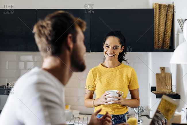 Portrait of young woman smiling at boyfriend with laptop in the kitchen