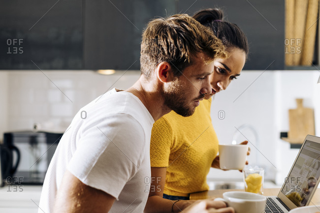 Young couple sharing laptop in the kitchen