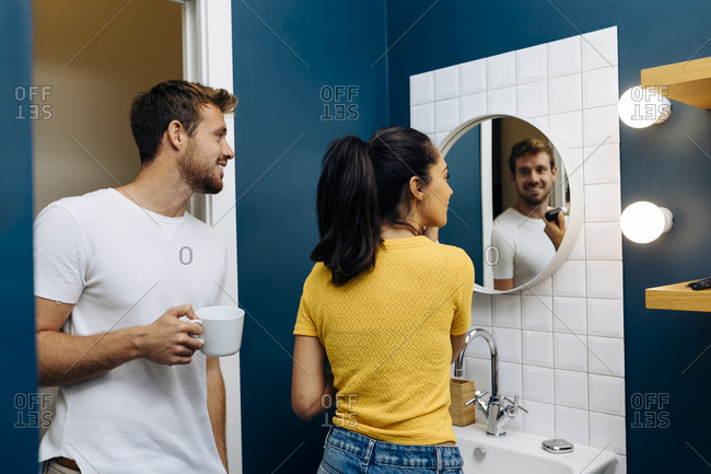 Smiling young man watching girlfriend applying make up