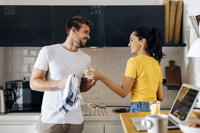 Happy young couple doing the dishes in the kitchen at home together