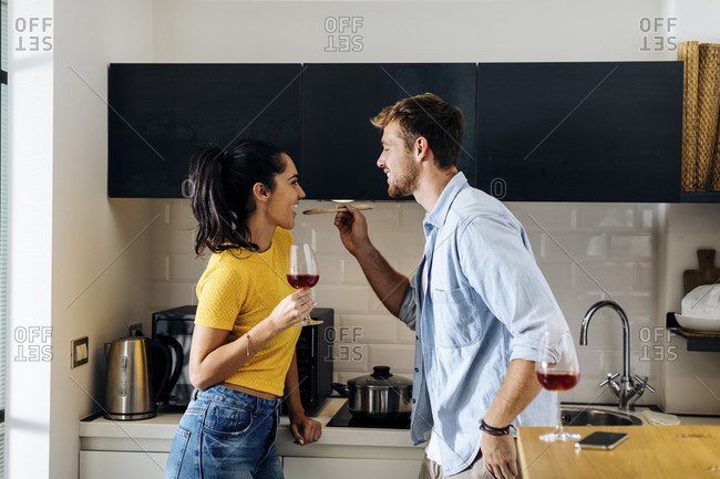 Happy young couple cooking and drinking wine in the kitchen at home together
