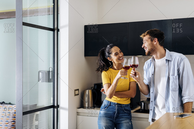 Happy young couple drinking wine in the kitchen at home together
