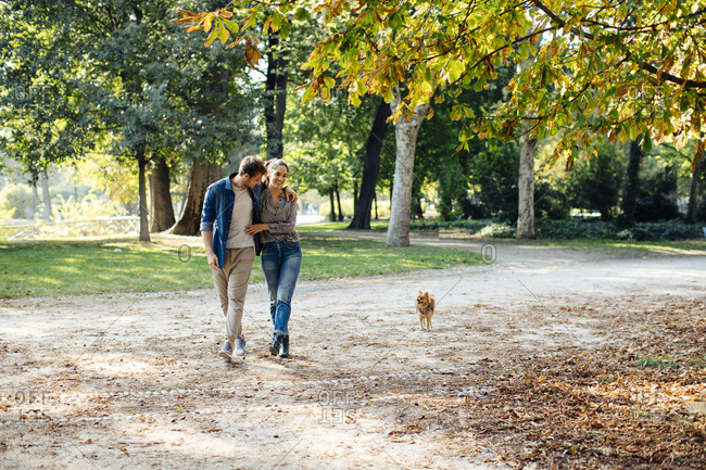 Happy young couple with dog in a park
