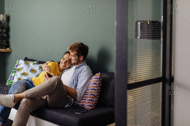 Happy affectionate young couple sitting on the couch at home