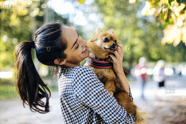 Happy young woman holding dog in a park