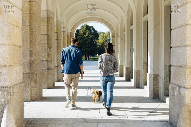 Rear view of young couple walking with dog in an arcade