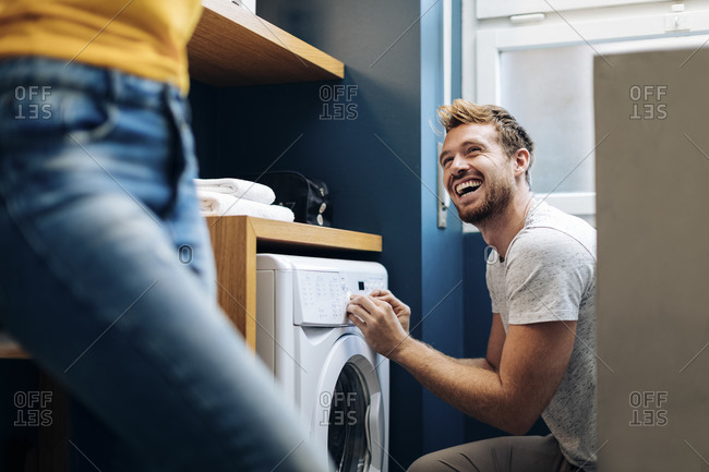 Happy young man looking at girlfriend and doing the laundry at home