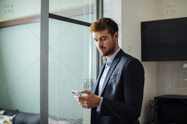 Young businessman using cell phone at home
