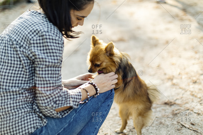 Young woman playing with dog outdoors