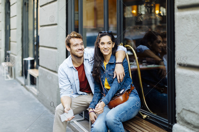 Happy young couple sitting on windowsill in the city- Milan- Italy