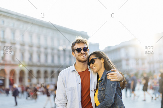 Happy young couple on a square in the city at sunset- Milan- Italy