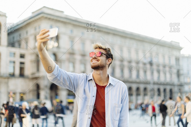 Smiling young man taking a selfie in the city- Milan- Italy