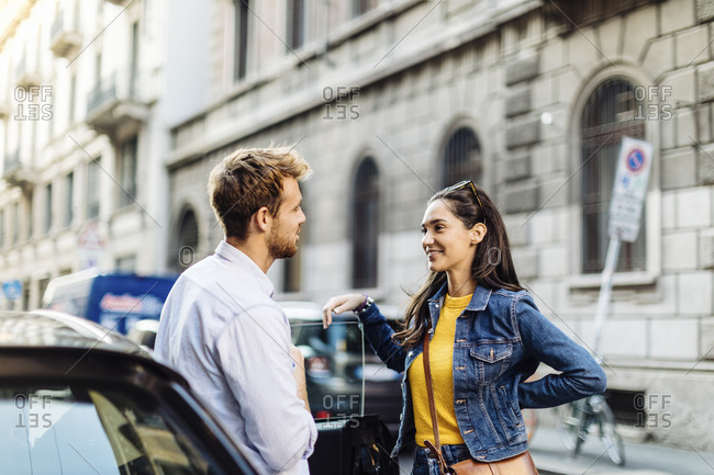 Young couple talking at a car in the city- Milan- Italy