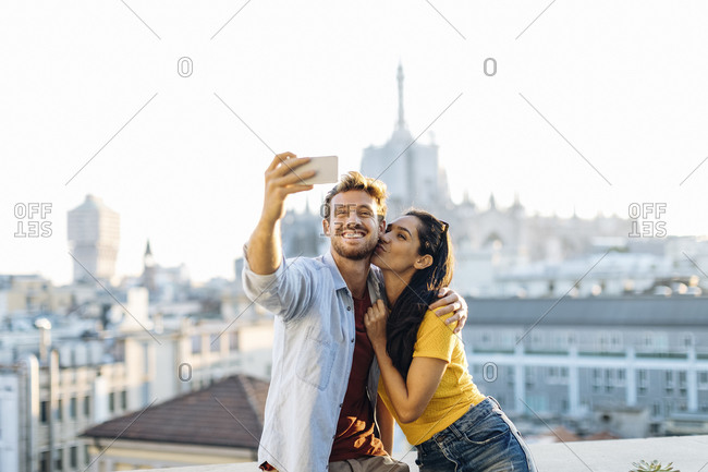 Happy young couple taking a selfie above the city- Milan- Italy