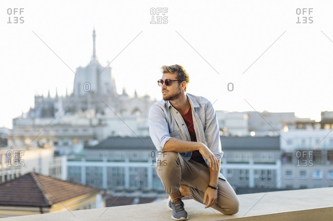 Young man crouching on a balcony above the city- Milan- Italy