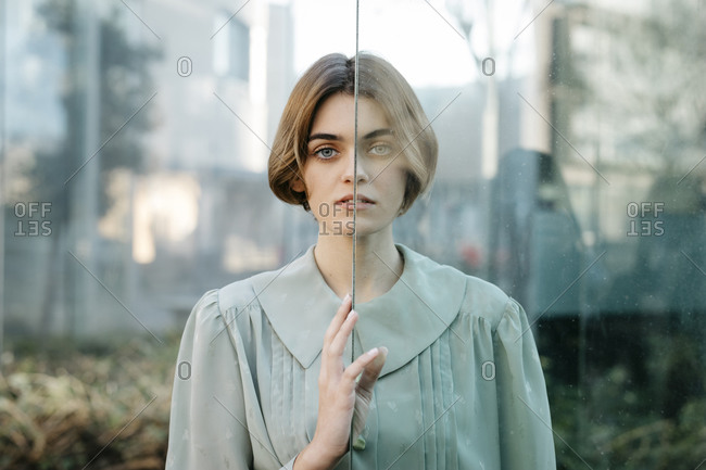 Portrait of woman with half of her face behind a glass