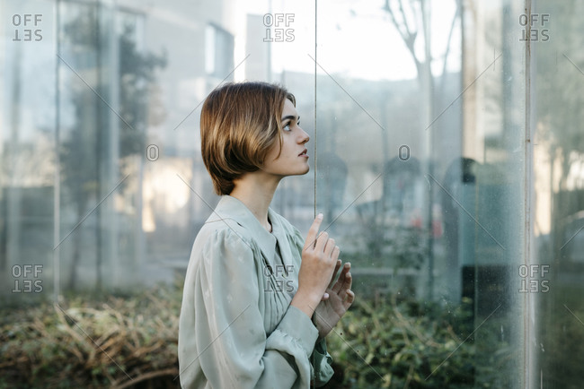 Portrait of woman with her face at a glass pane