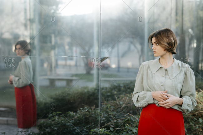 Portrait of woman with vintage clothes in an urban garden with reflection in the glass pane