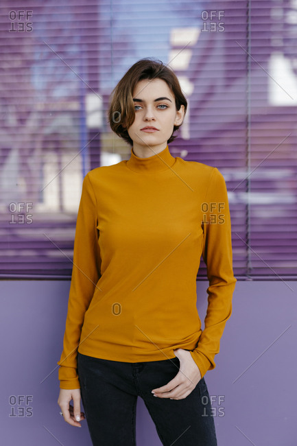 Portrait of young woman wearing orange turtleneck pullover- purple glass wall in the background