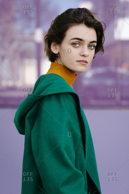 Young woman wearing green coat in front of a glass pane