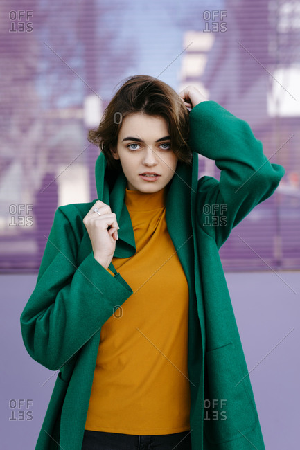 Young woman wearing green coat in front of purple glass pane