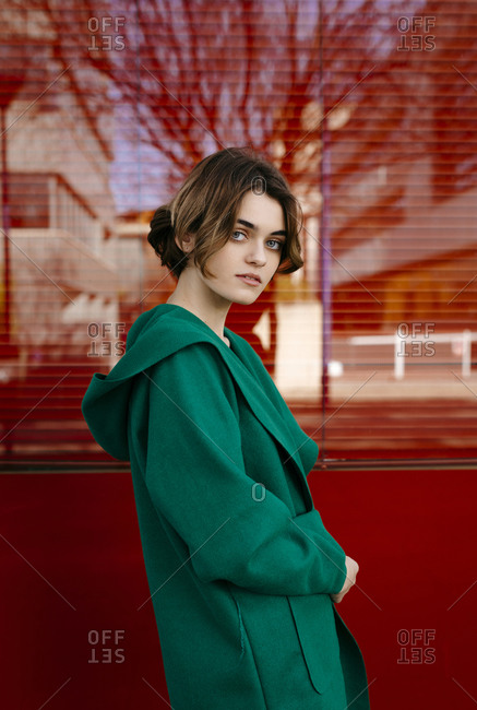 Young woman wearing green coat in front of a red glass pane