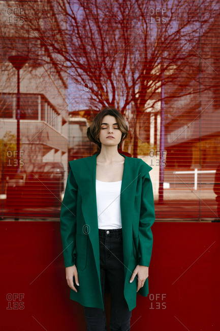 Young woman with closed eyes wearing green coat in front of a glass pane