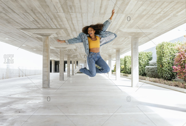 Smiling woman jumping in empty parking deck