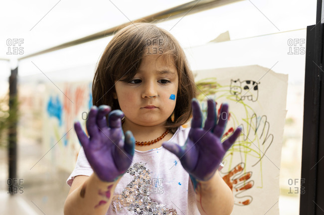 Little girl messing around with her painted hands