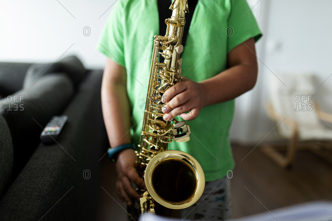 Boy exercising to play the saxophone at home