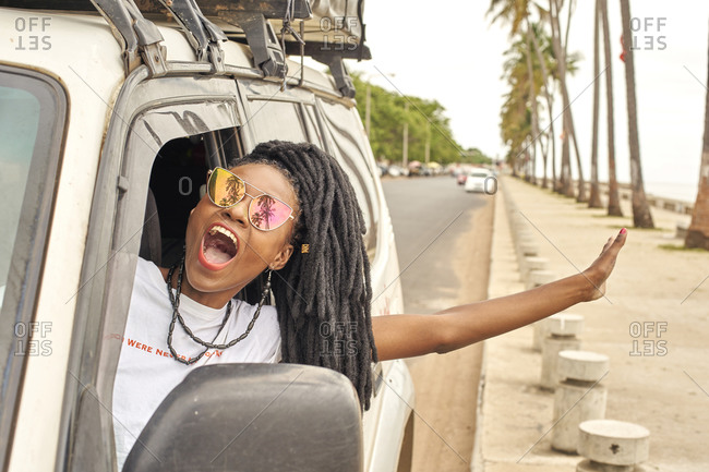 Portrait of screaming woman with dreadlocks leaning out of car window- Maputo- Mozambique