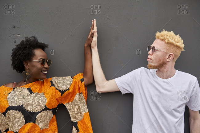 Couple joining hands in front of grey background