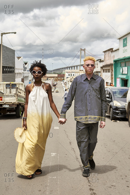 Portrait of fashionable couple walking hand in hand on the street- Maputo- Mozambique