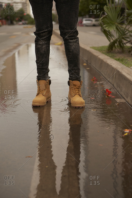 Legs of young man standing in a puddle