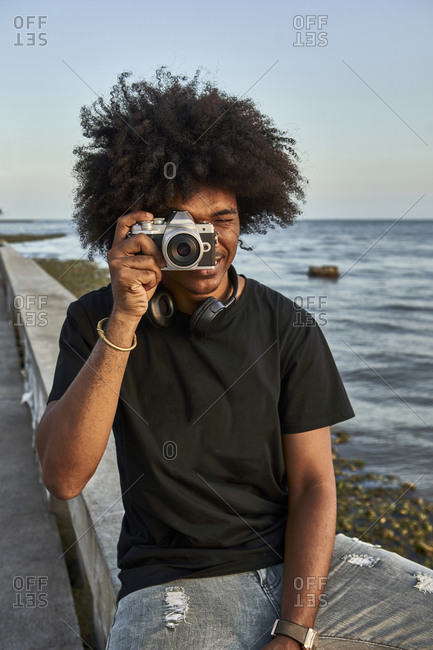 Young man sitting on wall and photographing with his camera at seafront