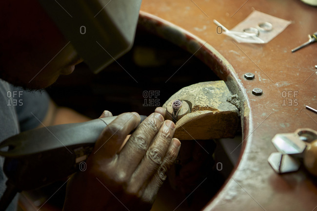 Man repairing a ring with a missing diamond