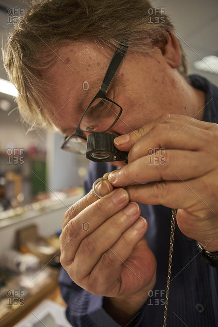 Senior man checking the diamond on a ring with a magnifying glass