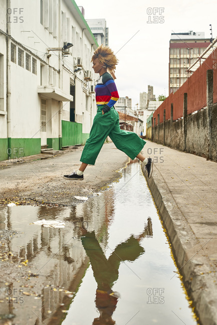 Young woman jumping over puddle on a street