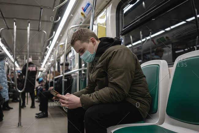 Young man in commuter train- wearing face mask- using smartphone