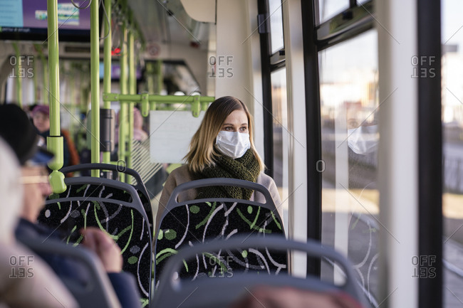 Woman with face mask sitting in tram